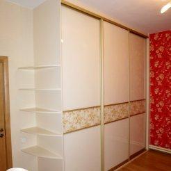 Белый шкаф-купе с тремя дверями и открытыми боковыми полками в спальню